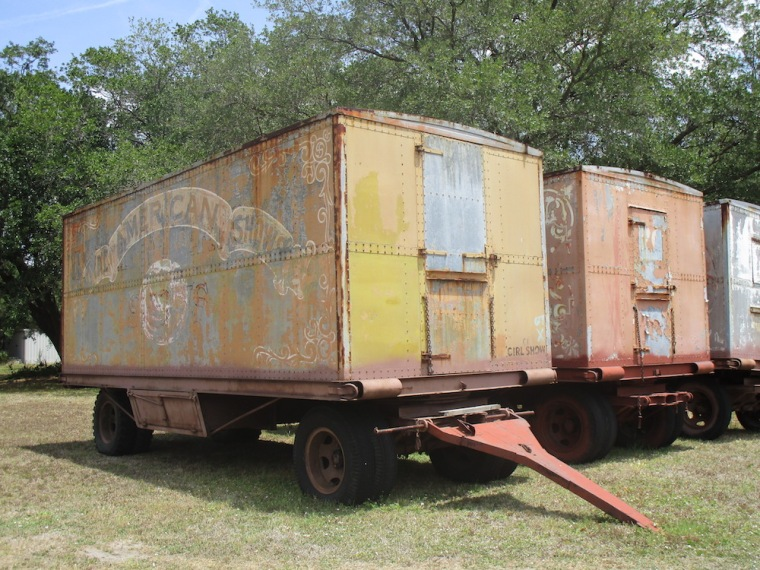"Old trailers from the American Circus — the one in the foreground is modestly labeled ""Girl Show."""